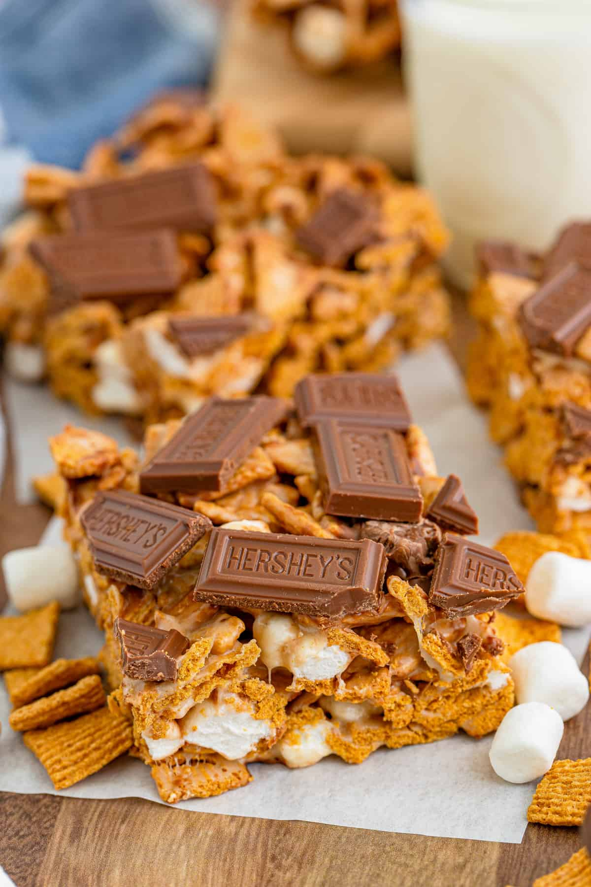 S'mores bars on parchment paper surrounded by marshmallows and Golden Grahams