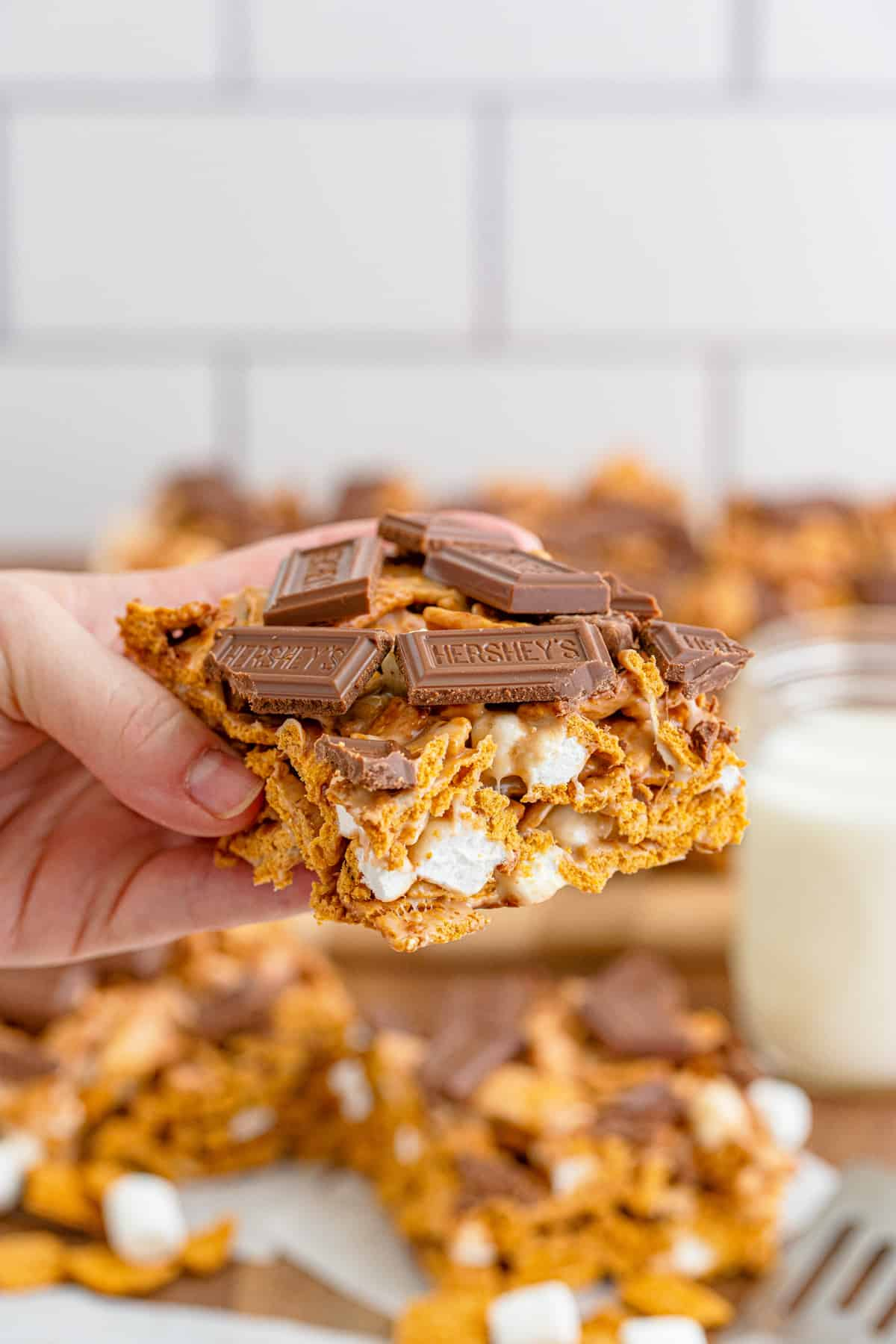 Hand holding up one S'mores Bar showing the inside and chocolate topping