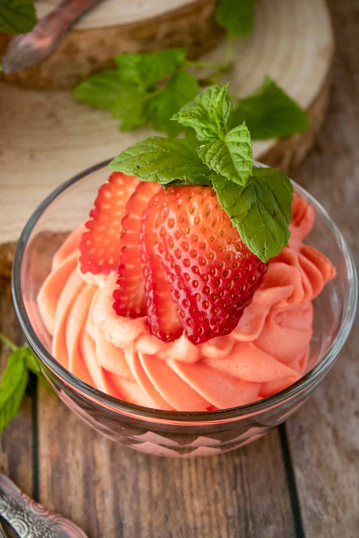 Overhead photo of Strawberry Mousse in bowl with strawberry and mind