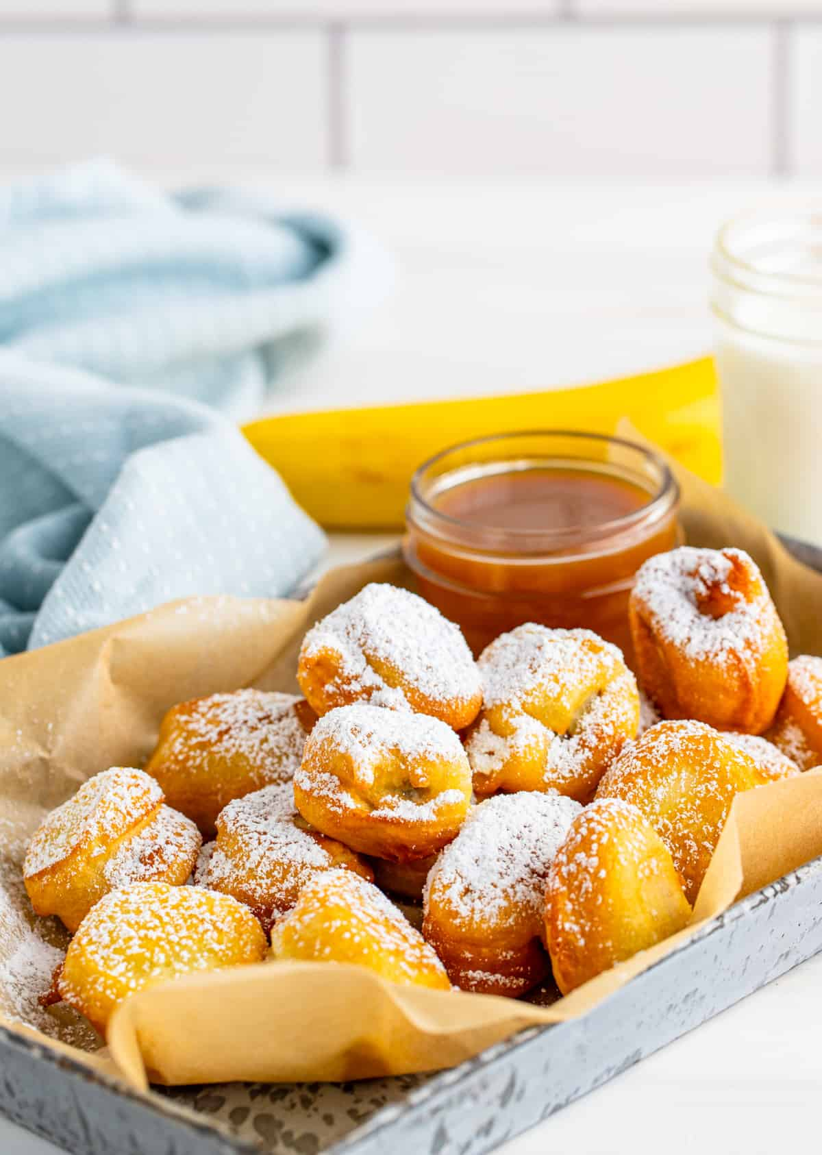Banana Funnel Cake Bites on silver tray with parchment paper