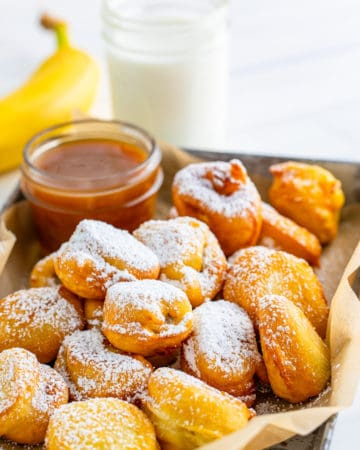 Funnel Cake Bites on silver tray with banana in background with milk