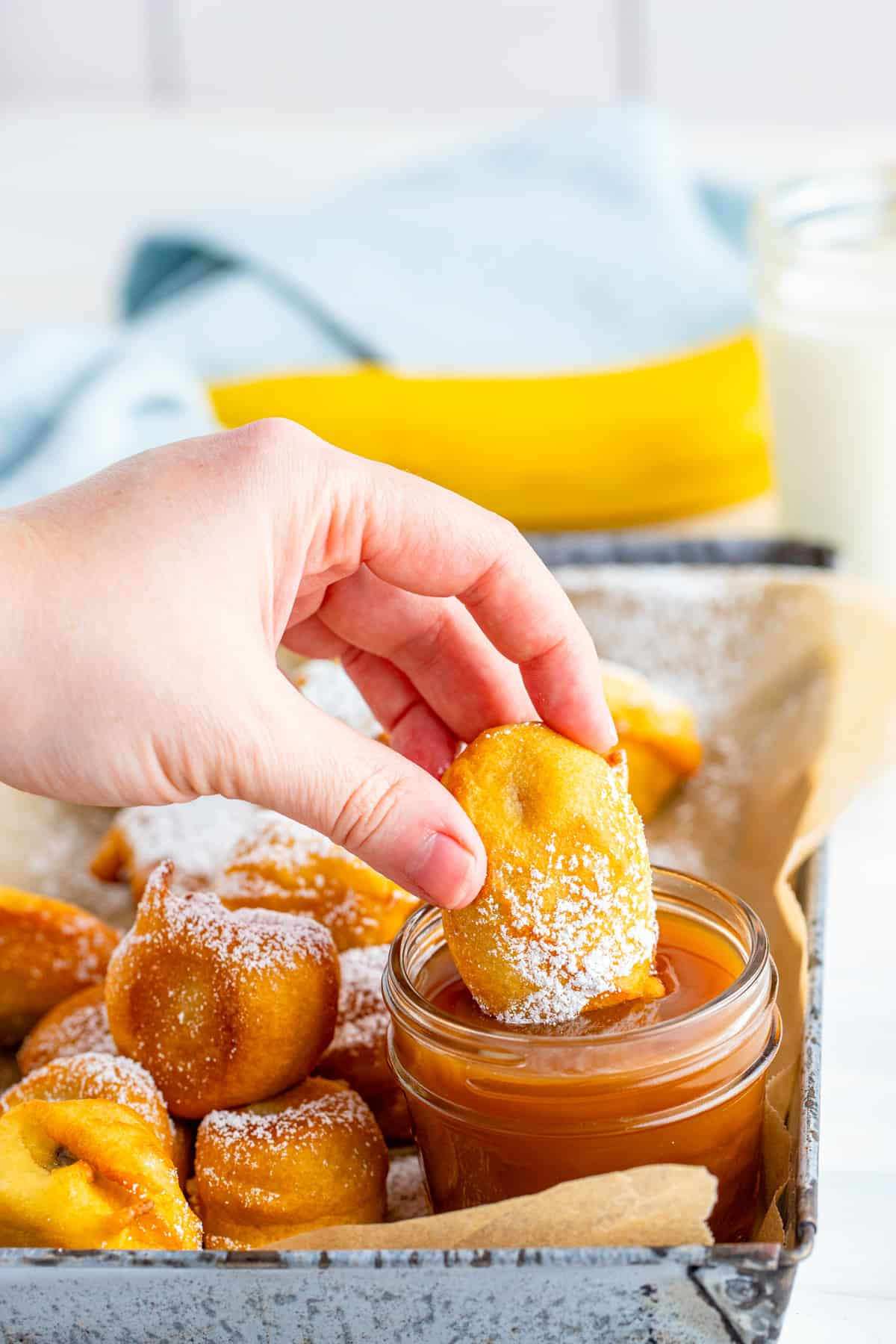 Hand dipping one Funnel Cake Bite into caramel sauce