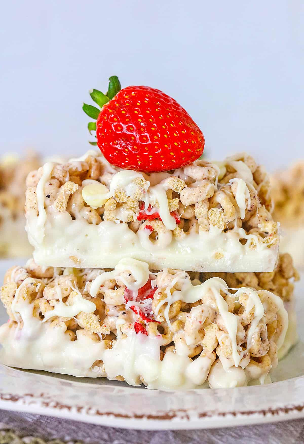 Close up of two stacked Cereal Bars with strawberry on top