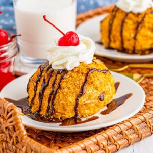 Square image of one Fried Ice Cream Recipe on white plate topped with chocolate syrup, whipped cream and cherry