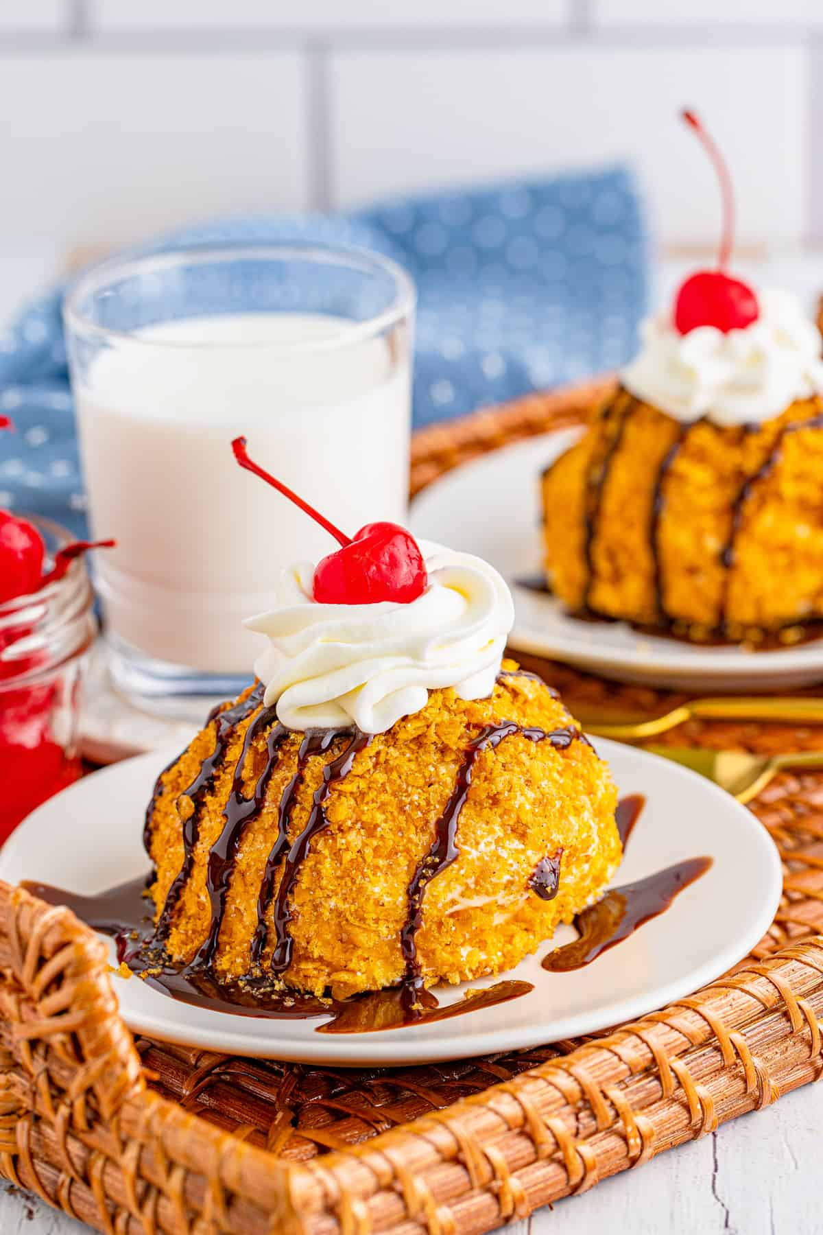 Fried Ice Cream Recipe on white plates on wicker tray with milk in background