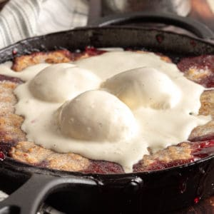 Square image of finished cobbler in pan with ice cream