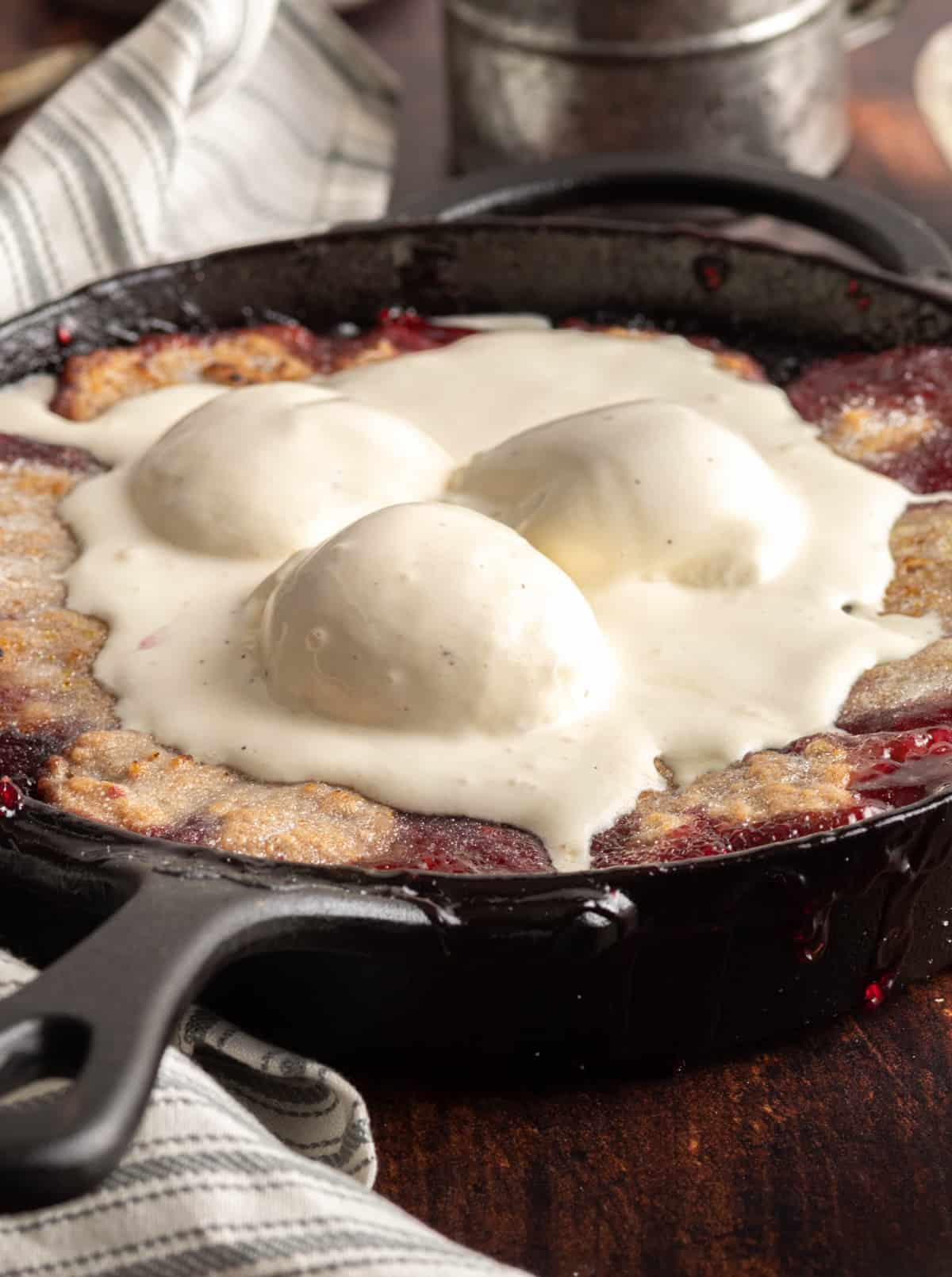 Ice cream on finished Berry Cobbler in cast iron skillet