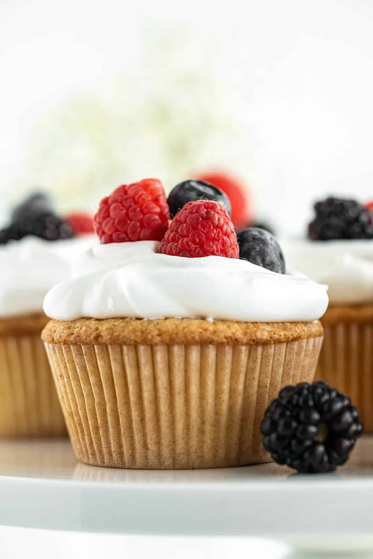 One cupcake topped with whipped cream and berries