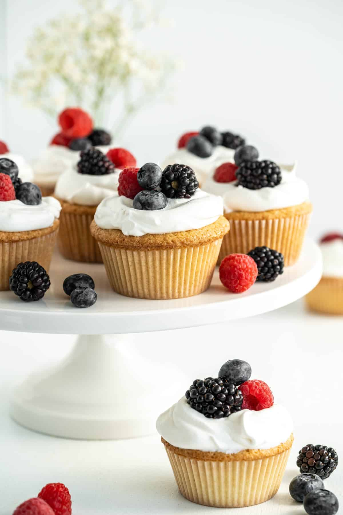 Cake stand with cupcakes and one cupcake below with fruit