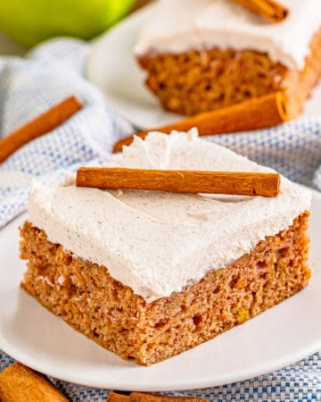 Square image of Apple Cinnamon Cake on white plate topped with cinnamon stick.
