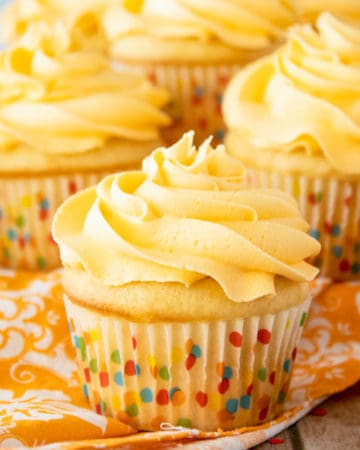 Square image of frosting on vanilla cupcakes.