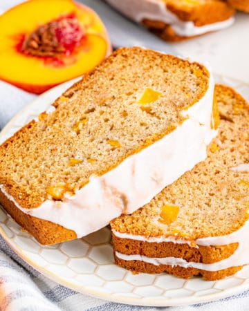 Square image of two slices of glazed Peach Bread on plate.