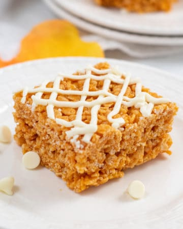 Square photo of one Rice Krispie Treat on white plate with white chocolate chips
