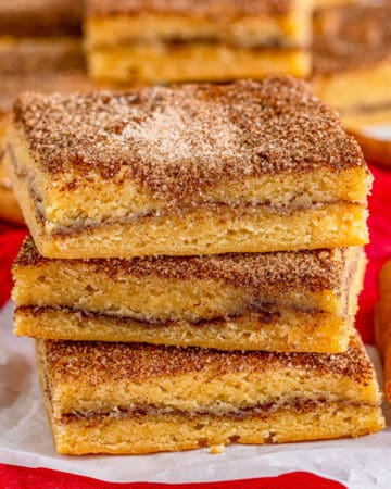 Square image of three stacked Snickerdoodle Bars on parchment paper.